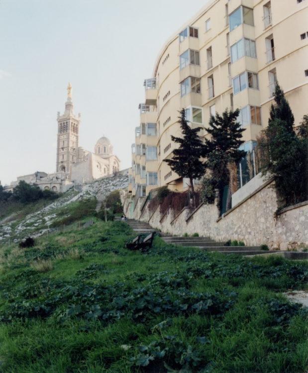 Anne Loubet | Marseille les collines | 2006-2020 | BASILIQUE NOTRE DAME DE LA GARDE VUE DEPUIS LES ESCALIERS DE LA MONTÉE COMMANDANT RENÉ VALENTIN, AVEC L'IMMEUBLE COURBE LES HORIZONS CLAIRS, QUARTIER ROUCAS BLANC MARSEILLE 7