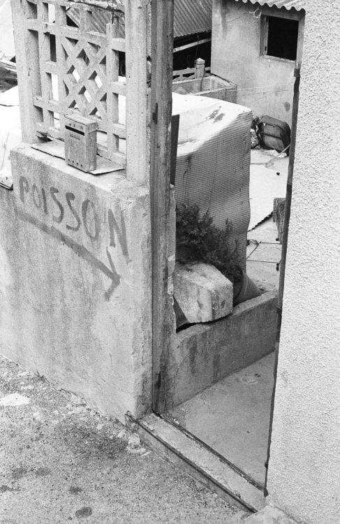 Fabrice Ney | Fos-sur-Mer : regard sur un quotidien localisé | 1977-1979 | Extrait du Fond FOS-SUR-MER - 1979 - Série Cente Ville - sous-série portail : Centre ancien, clôture béton, inscription peinte POISSON.