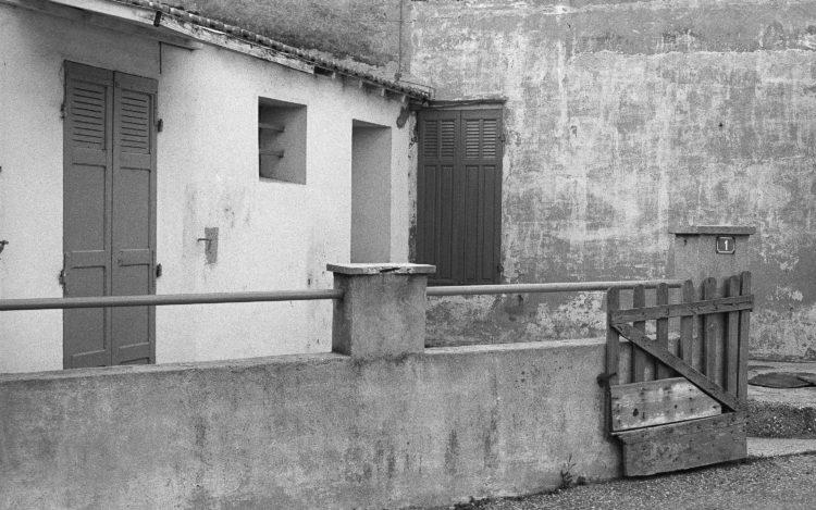 Fabrice Ney | Fos-sur-Mer : regard sur un quotidien localisé | 1977-1979 | Extrait du Fond FOS-SUR-MER - 1979 - Série Cente Ville: quartier populaire périphérique à l'ancienne cartonnerie Voisin Pascal - espace privatif d'accès à l'entrée, muret,  volets fermés