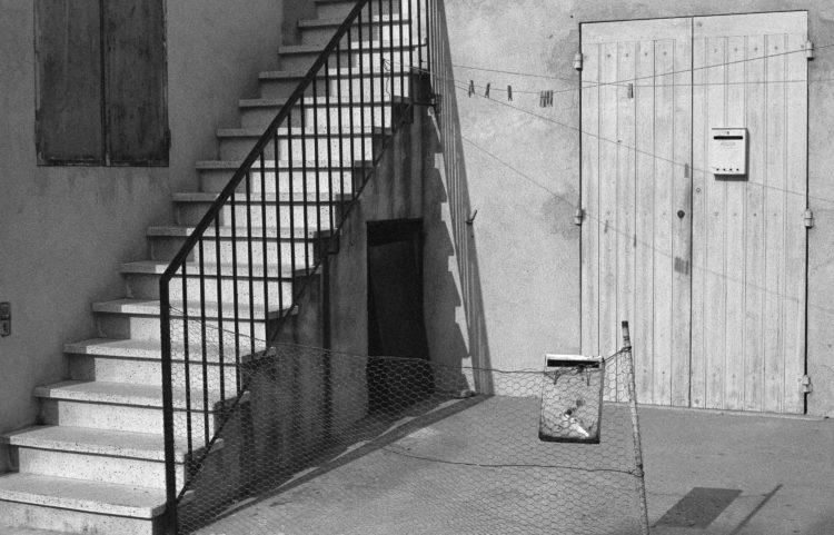 Fabrice Ney | Fos-sur-Mer : regard sur un quotidien localisé | 1977-1979 | Extrait du Fond FOS-SUR-MER - 1979 - Série Centre Ville: porte d'entrée rez de chaussée fermée par des volets avec une boîte au lettre, étendage vide, escalier extérieur d'accès au premier niveau, deuxième boîte au lettre accrochée sur un grillage.