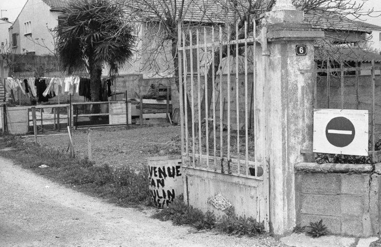 Fabrice Ney | Fos-sur-Mer : regard sur un quotidien localisé | 1977-1979 | Extrait du Fond FOS-SUR-MER - 1979 - - Série Centre Ville: rue Jean Moulin, périphérique en bordure  des salins, panneau sens interdit peint à la main sur la grille,  jardin et linge étendu en arrière plan.