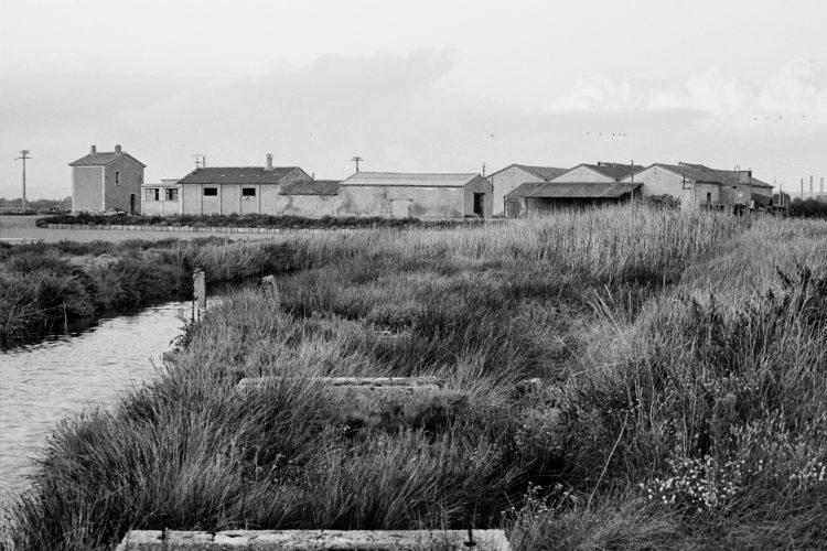 Fabrice Ney | Soude | 1988-1994 | Extrait de SOUDE-Vestiges de l'industrie chimique au XIXème siècle dans les Bouches-du-Rhône - 1988-1993. Série Salins de Berre l'Etang. Canal et vue arrière d'ensemble des bâtiments techniques des salins, à gauche le poste de douane.