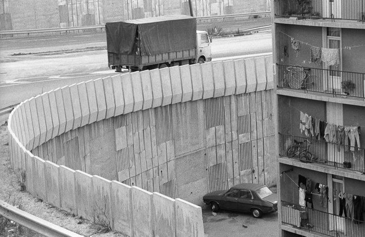 Fabrice Ney | ZUP n°1 | 1980-1983 | Extrait de ZUP n°1 - Marseille  - 1981-1983.  Extrémité sud du Bâtiment P , voiture en contrebas, rambarde béton de la voie d'accès à l'avenue S. Allende, présence d'un camion de passage.