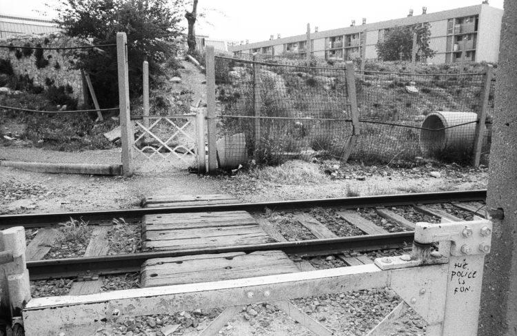 Fabrice Ney | ZUP n°1 | 1980-1983 | Extrait de ZUP n°1 - Marseille  - 1981-1983.  Passage piéton, voie ferrée une voie, grillage et graffiti sur le portique