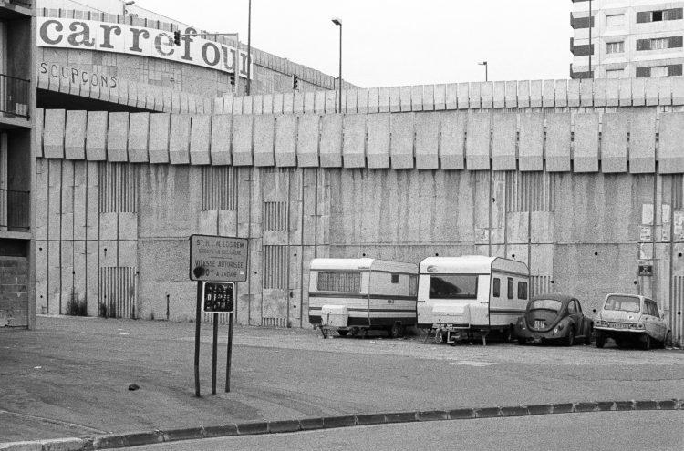 Fabrice Ney | ZUP n°1 | 1980-1983 | Extrait de ZUP n°1 - Marseille  - 1981-1983.  Rue de la Busserine, caravanes et voitures garées Panneau Logirem, Carrefour, graffiti