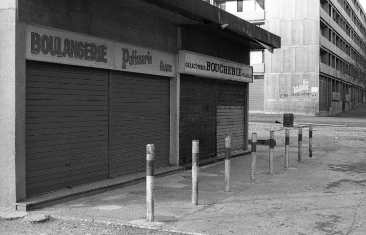 Fabrice Ney | ZUP n°1 | 1980-1983 | Extrait de ZUP n°1 - Marseille  - 1981-1983.  Commerces au premier plan : boulangerie et boucherie, poteaux de limitation d'accès. Arrière plan graffiti