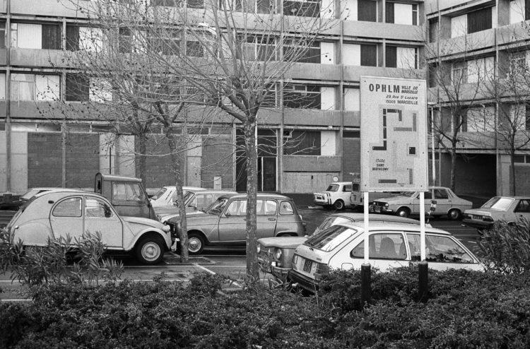 Fabrice Ney | ZUP n°1 | 1980-1983 | Extrait de ZUP n°1 - Marseille  - 1981-1983.  Plan signalétique au premier plan, haie végétale, parking, arbres, façade d'immeuble en arrière plan.