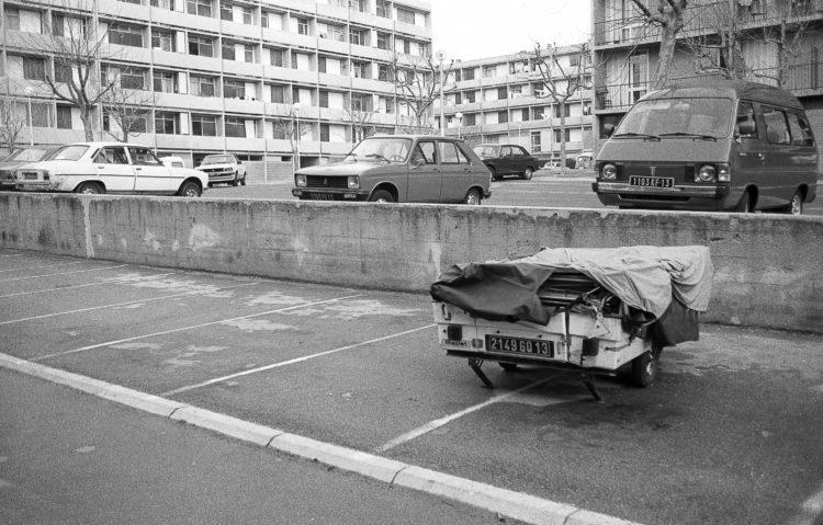 Fabrice Ney | ZUP n°1 | 1980-1983 | Extrait de ZUP n°1 - Marseille  - 1981-1983.  Parking, voitures garées, façades d'immeuble, remorque de camping au premier plan.
