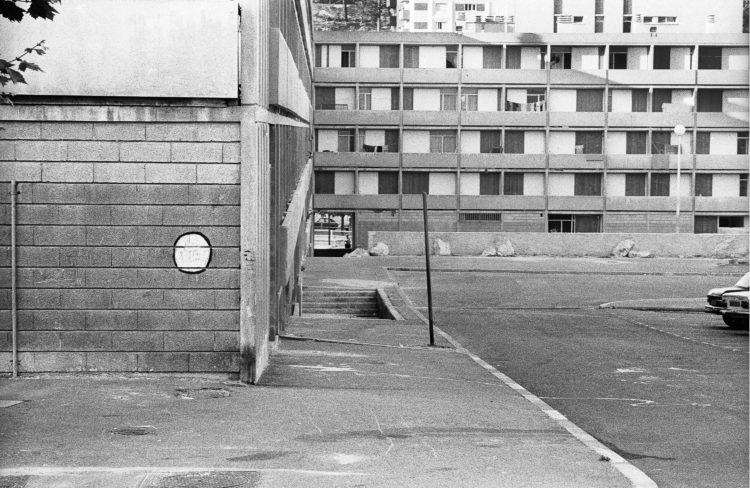 Fabrice Ney | ZUP n°1 | 1980-1983 | Extrait de ZUP n°1 - Marseille  - 1981-1983.  Angle nord du E, parking,  parcelle enclavée et en contrebas, muret béton et rochers pour limiter l'accès aux véhicules.