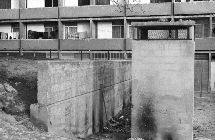 Fabrice Ney | ZUP n°1 | 1980-1983 | Extrait de ZUP n°1 - Marseille  - 1981-1983.  Remblai de terre contenu par un mur de béton, bâti technique, poteau, vue sur balcon, linge étendu, graffiti gravé «Nadine+Lionel».
