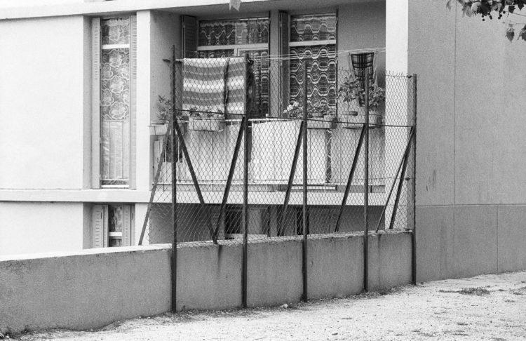 Fabrice Ney | ZUP n°1 | 1980-1983 | Extrait de ZUP n°1 - Marseille  - 1981-1983.  Grillage disposé sur poteau en fer fixé sur un muret en béton, Balcon au premier niveau, pots de fleur, rideaux aux fenêtres, couverture étendue.