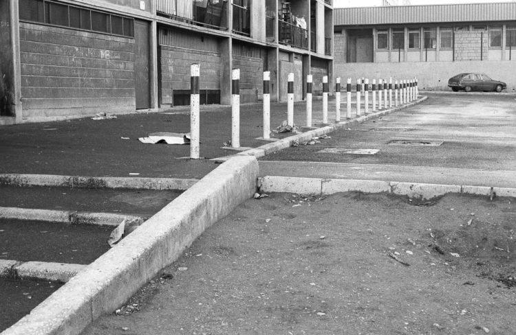 Fabrice Ney | ZUP n°1 | 1980-1983 | Extrait de ZUP n°1 - Marseille  - 1981-1983. Poteaux limitant l'accès au trottoir, rez-de-chaussée façade béton, graffitis, Maison pour tous en arrière plan.