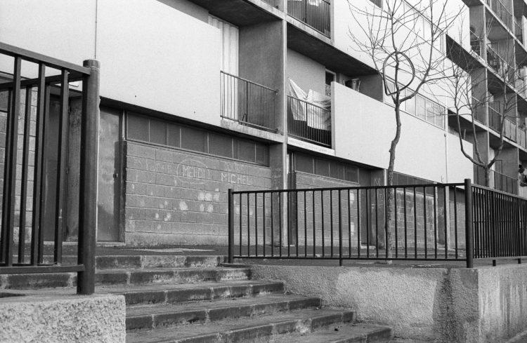 Fabrice Ney | ZUP n°1 | 1980-1983 | Extrait de ZUP n°1 - Marseille  - 1981-1983.  Escalier, rambarde métallique, arbuste avec pneu de vélo accroché dans les branches, graffiti, sol mouillé, Panneau