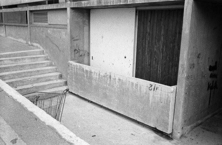 Fabrice Ney | ZUP n°1 | 1980-1983 | Extrait de ZUP n°1 - Marseille  -  1981-1983. Muret en béton, caddy, escalier, balcon de rez-de-chaussée fermée, graffitis, angle du passage sous l'immeuble E