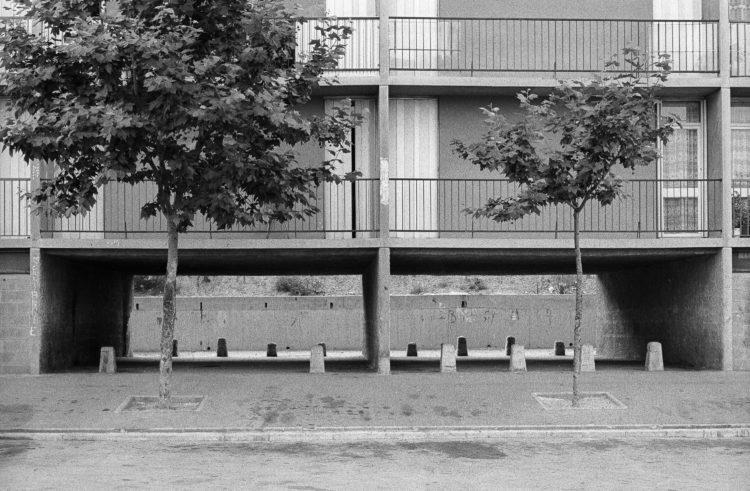 Fabrice Ney | ZUP n°1 | 1980-1983 | Extrait de ZUP n°1 - Marseille  - 1981-1983. Passage en rez-de-chaussée, deux arbres,  Balcons des premier et deuxième niveau, plots empêchant le passage des voitures.
