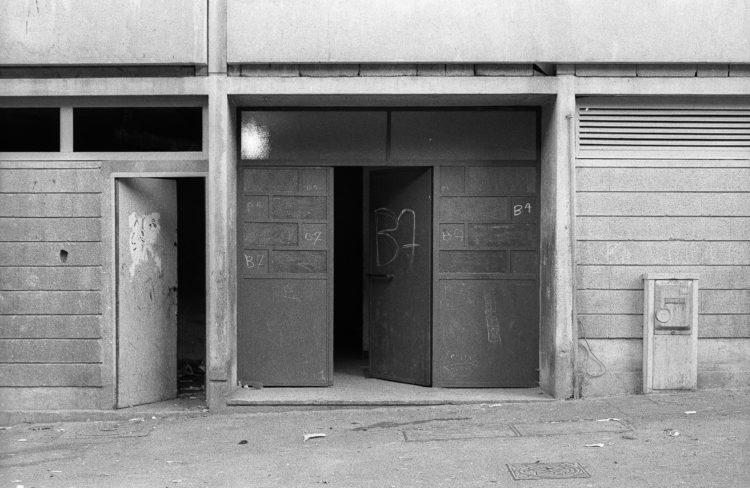 Fabrice Ney | ZUP n°1 | 1980-1983 | Extrait de ZUP n°1 - Marseille  - 1981-1983. Porte en fer et verre et porte de service ouverte, inscription manuscrite répétée