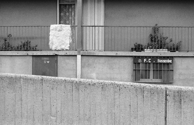 Fabrice Ney | ZUP n°1 | 1980-1983 | Extrait de ZUP n°1 - Marseille  - 1981-1983. Vue frontale de la façade du bâtiment P. Un muret en béton au premier plan. Ecriteau