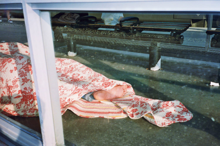 Sam Phelps | Belladone | 2017-2020 | A man sleeps on the ground on the train platform at Saint Charles station in Marseille, France, 2019.