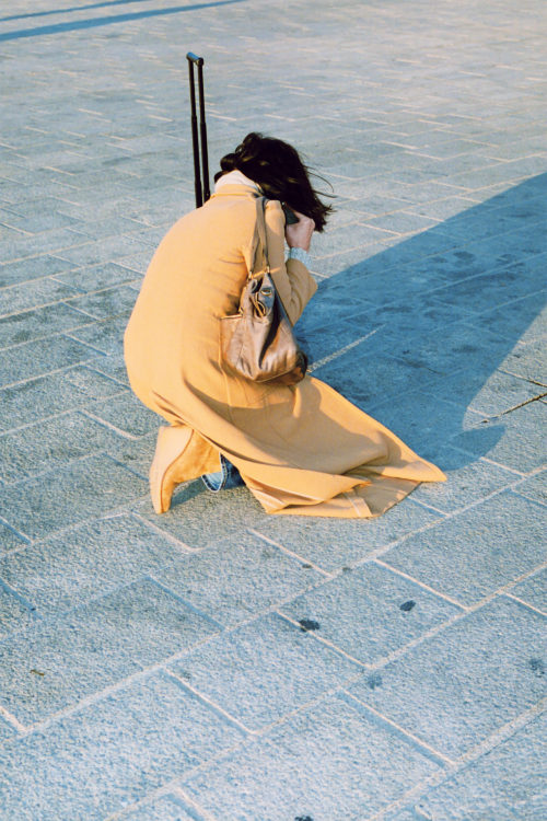 Sam Phelps   Belladone   2017-2020   A woman crouches down at the Vieux Port in Marseille, France, 2019.