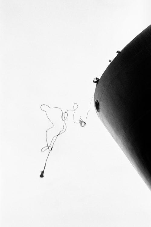 Gestes du travail | Photographie en noir et blanc d'une amare lancée du haut d'un bateau pétrolier et formant un homme dans le ciel