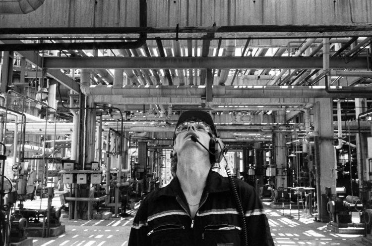 Franck Pourcel | La petite mer des oubliés – Gestes du travail | 1996-2006 | Gestes du travail | Photographie en N/B d'un homme au travail dans une usine pétrochimique. L'hommeau milieu des tuyaux lève la tête pour surveiller.