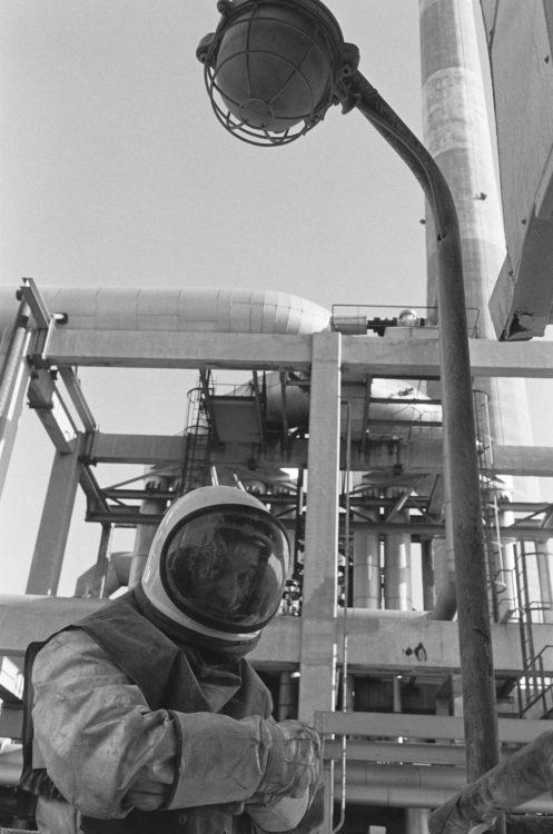 Franck Pourcel | La petite mer des oubliés – Gestes du travail | 1996-2006 | Gestes du travail | Photographie en noir et blanc d'un homme en scaphandre dans l'usine pétrochimique de Martigues.