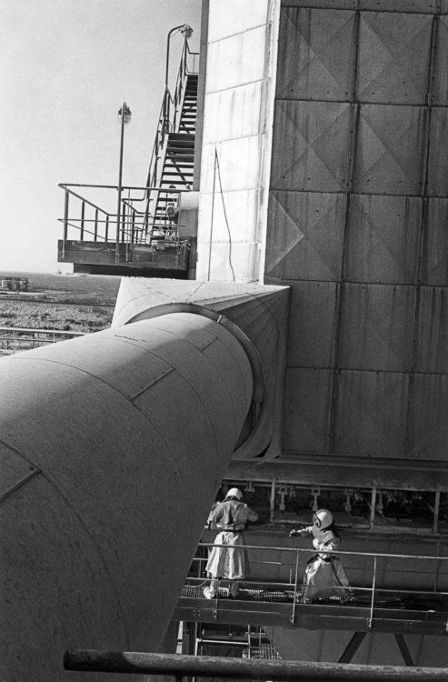 Franck Pourcel | La petite mer des oubliés – Gestes du travail | 1996-2006 | Gestes du travail | Photographie en N/B de deux hommes en scaphandre travaillant sur une unité dangeureuse
