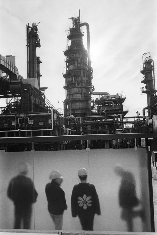 Franck Pourcel | La petite mer des oubliés – Gestes du travail | 1996-2006 | Gestes du travail | Photographie en noir et blanc de personnes attendant le bus devant une usine pétrochimique. Une des personnes a un pull avec une fleur tricotée