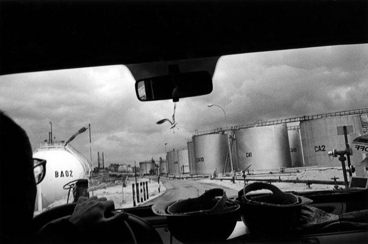 Franck Pourcel | La petite mer des oubliés – Gestes du travail | 1996-2006 | Gestes du travail | Photographie en N/B d'une usine pétrochimique depuis la voiture d'un travailleur avec un gabian en face