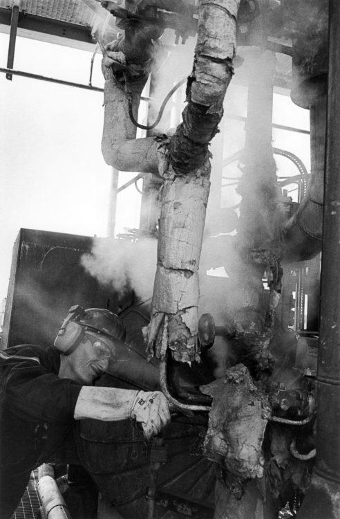 Franck Pourcel | La petite mer des oubliés – Gestes du travail | 1996-2006 | Gestes du travail | Photographie en N/B d'un homme tournant un volant d'une vanne dans une unité de travail
