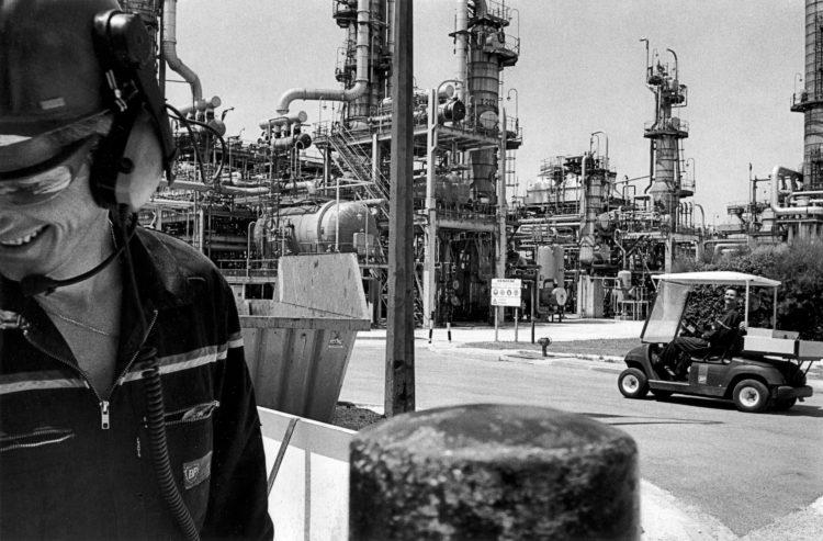 Franck Pourcel | La petite mer des oubliés – Gestes du travail | 1996-2006 | Gestes du travail | Photographie en N/B de deux hommes qui se parlent dans une unité de travail