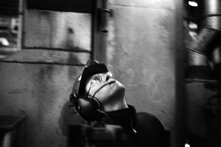 Franck Pourcel | La petite mer des oubliés – Gestes du travail | 1996-2006 | Gestes du travail | Photographie en N/B d'un homme qui lève la tête avec son casque et son micro dans l'usine pétrochimique