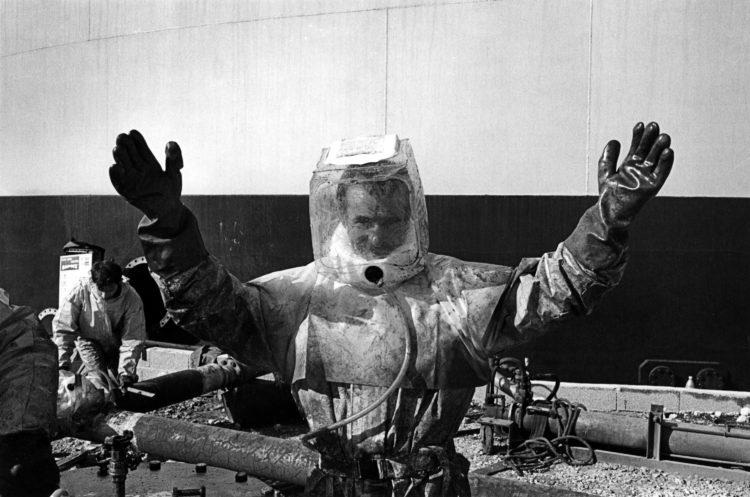 Franck Pourcel | La petite mer des oubliés – Gestes du travail | 1996-2006 | Gestes du travail | Photographie en N/B d'un travail intérim qui lève les bras et fait le signe de la victoire.