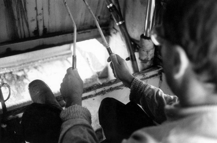 Franck Pourcel | La petite mer des oubliés – Gestes du travail | 1996-2006 | Gestes du travail | Photographie en N/B d'un homme qui tient des manettes à l'intérieur d'un machine qui récupère le sel