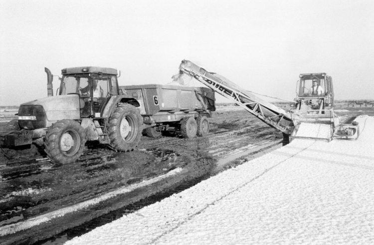 Franck Pourcel | La petite mer des oubliés – Gestes du travail | 1996-2006 | Gestes du travail | Photographie en N/B d'une machine qui récupère la couche de sel et l'envoi dans la benne d'un camio qui roule à côté