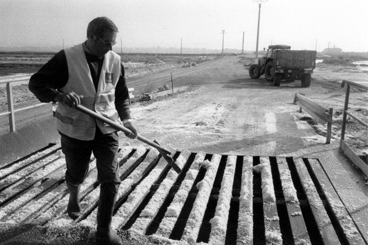 Franck Pourcel | La petite mer des oubliés – Gestes du travail | 1996-2006 | Gestes du travail | Photographie en N/B d'un homme qui passe une raclette pour nettoyer et envoyer le sel à travers la grille après le versement d'un tracteur