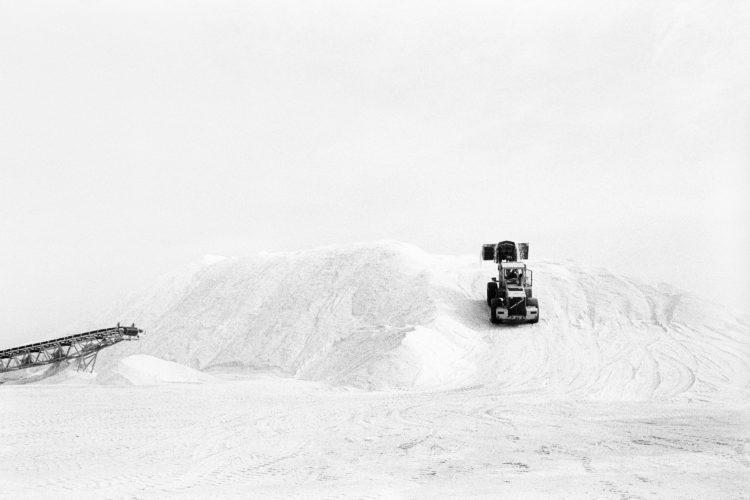 Franck Pourcel | La petite mer des oubliés – Gestes du travail | 1996-2006 | Gestes du travail | Photographie en N/B d'un engin qui monte sur un tas de sel.