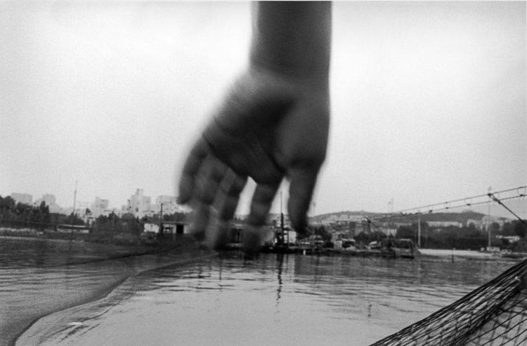 Franck Pourcel | La petite mer des oubliés – Gestes du travail | 1996-2006 | Gestes du travail | Photographie en N/B d'une main au dessus de filet de pêche sur un canal