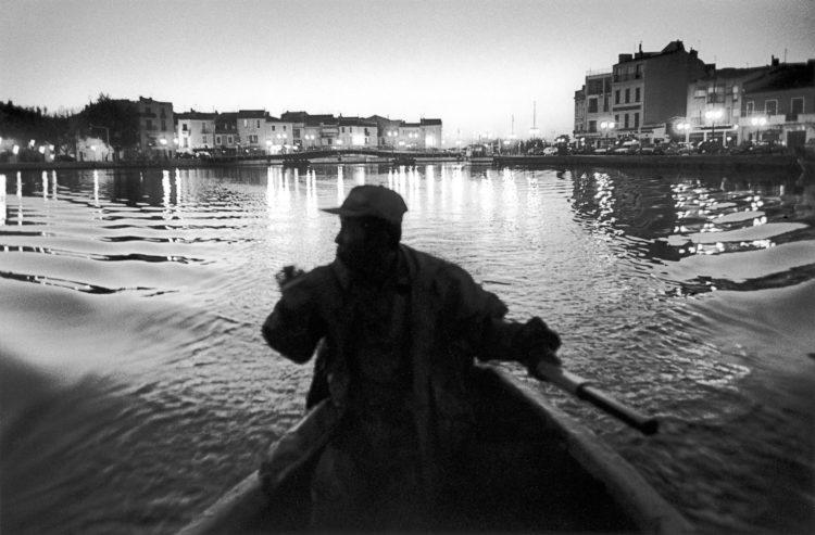 Franck Pourcel | La petite mer des oubliés – Gestes du travail | 1996-2006 | Gestes du travail | Photographie en N/B d'un pêcheur dans sa barque sur un canal dans la ville de Martigues