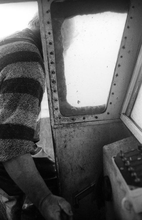 Franck Pourcel | La petite mer des oubliés – Gestes du travail | 1996-2006 | Gestes du travail | Photographie en N/B d'un pêcheur qui conduit son bâteau depuis l'extérieur