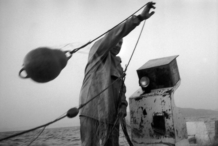 Franck Pourcel | La petite mer des oubliés – Gestes du travail | 1996-2006 | Gestes du travail | Photographie en N/B d'un pêcheur qui remonte sa bouée de marquage