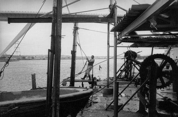 Franck Pourcel | La petite mer des oubliés – Gestes du travail | 1996-2006 | Gestes du travail | Photographie en N/B d'un pêcheur qui tire le câble du calen