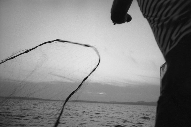 Franck Pourcel | La petite mer des oubliés – Gestes du travail | 1996-2006 | Gestes du travail | Photographie en N/B d'un pêcheur qui lance son filet dans l'eau