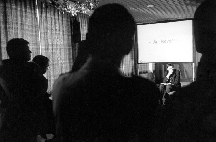 Franck Pourcel | La petite mer des oubliés – Luttes | 1996-2006 | Luttes | Photographie en N/B d'un homme assis devant un écran devant un groupe de personnes. Pot de départ du directeur de la raffinerie avec les cadres.