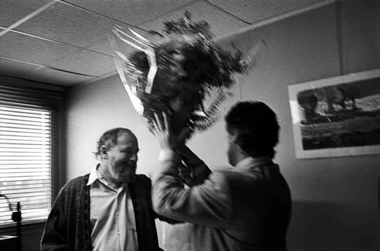 Franck Pourcel | La petite mer des oubliés – Luttes | 1996-2006 | Luttes | Photographie en noir et blanc de deux hommes montrant un bouquet de fleur. départ à la retraite et cadeau offert.
