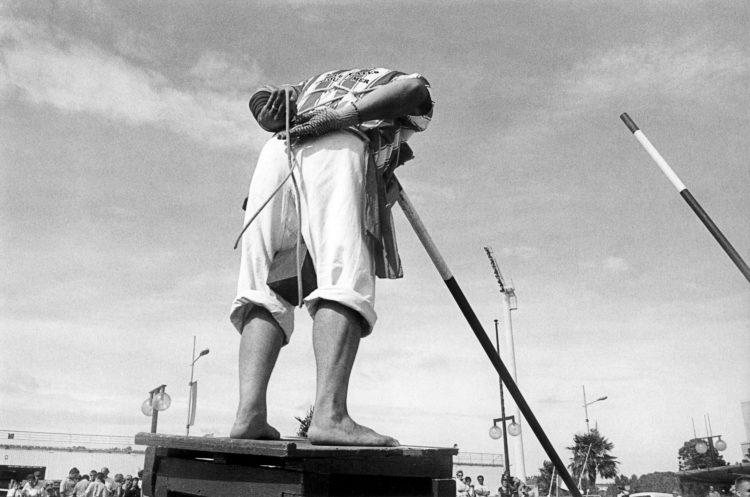Franck Pourcel | La petite mer des oubliés – Luttes | 1996-2006 | Luttes | Photographie en N/B d'un homme qui s'attache le plastron avant un match de joute provençale