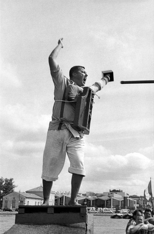 Franck Pourcel | La petite mer des oubliés – Luttes | 1996-2006 | Luttes | Photographie en N/B d'un homme venant de mettre à l'eau un autre homme dans le jeu de joute provençale