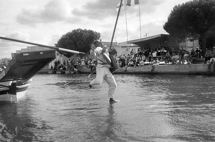 Franck Pourcel | La petite mer des oubliés – Luttes | 1996-2006 | Luttes | Photographie en N/B d'un homme qui tombe dans l'eau. après un jeu de joute provençale