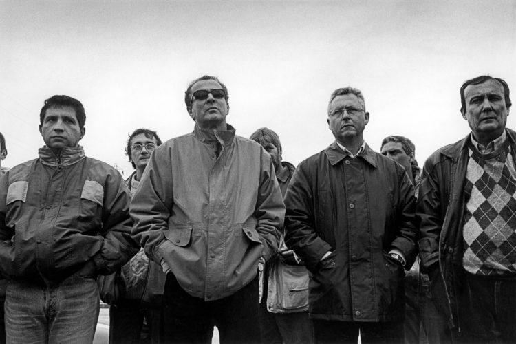 Franck Pourcel | La petite mer des oubliés – Luttes | 1996-2006 | Photographie en noir de plusieurs hommes faisant une manifestation devant l'usine pétrochimique.