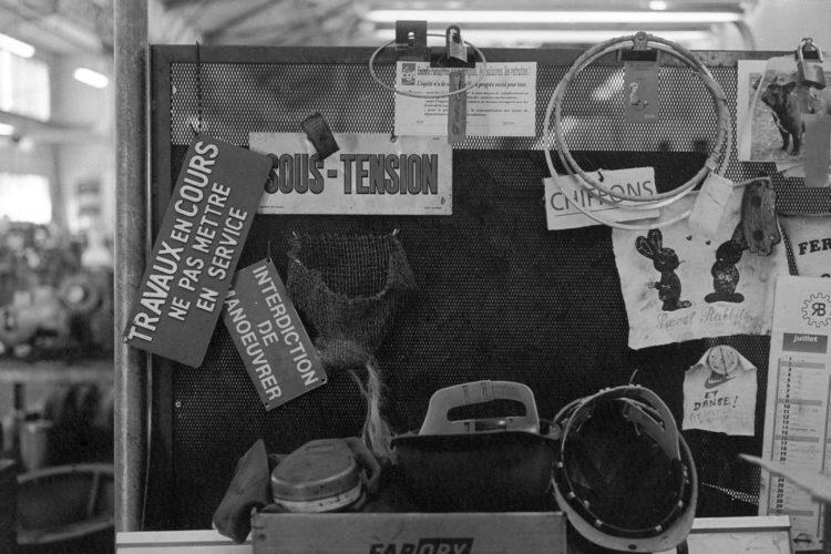 Franck Pourcel | La petite mer des oubliés – Luttes | 1996-2006 | Luttes | Photographie en N/B d'un tablier de travail avec diverses inscriptions et représentations